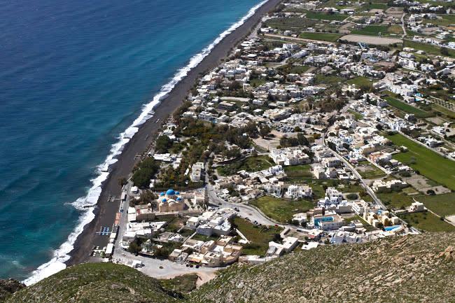 Perissa con la grande spiaggia scura, una delle più popolari di Santorini.